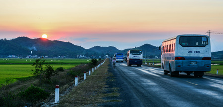 Nha Trang, Vietnam - Mar 20, 2016. Cars run on highway at sunset in Nha Trang, Vietnam. The total length of the Vietnam road system is about 222,179 km. Banco de Imagens - 120194574