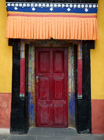 Wooden door of ancient Tibetan temple in Ladakh, North of India.