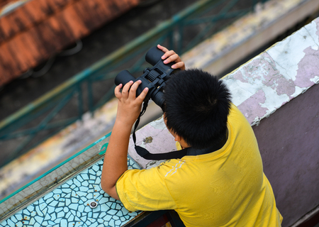 An Asian boy using the binocular at sunny day in Saigon, Vietnam.