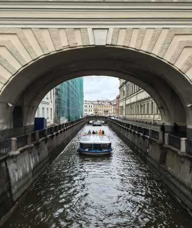 St. Petersburg, Russia - Oct 10, 2016. Tourist boat running on canal at rainy day in Saint Petersburg, Russia.