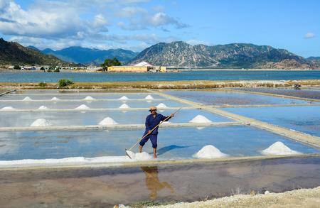 Nha Trang, Vietnam - Mar 21, 2016. A man working on salt field in Nha Trang, Vietnam. Salt fields is one of the most unique destinations in Nha Trang. 報道画像
