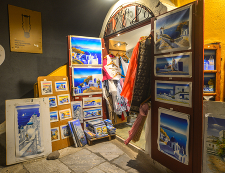 Santorini, Greece - Oct 9, 2018. Souvenir shop at night in Santorini Island, Greece. Santorini is one of the most popular islands for destination weddings and honeymoons. Imagens