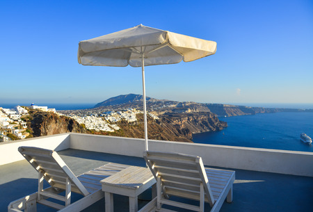 Seaview balcony with relaxing chairs and umbrella of white villa on Santorini Island in summer day.