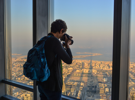 Dubai, UAE - Dec 7, 2018. A man enjoying at the observation deck of the highest building in the world, Burj al Khalifa. Редакционное