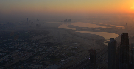 Aerial view of Dubai City at sunrise. View on the rooftop of Burj Khalifa Building.