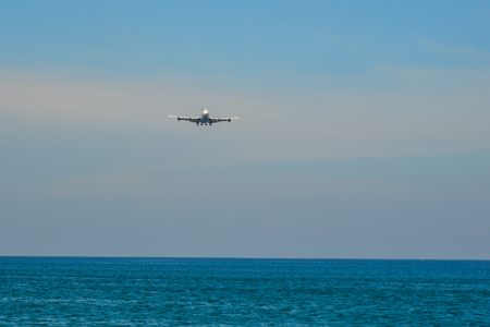 Passenger airplane landing above the blue sea near Phuket Airport (HKT).