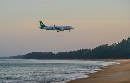 Phuket, Thailand - Apr 4, 2019. B-1026 Spring Airlines Airbus A320 flying over the sand beach at beautiful sunrise scenery on Phuket Island, Thailand. Imagens - 122862516