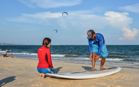 Phan Thiet, Vietnam - May 15, 2018. Surf school students training on the sand beach at summer day.