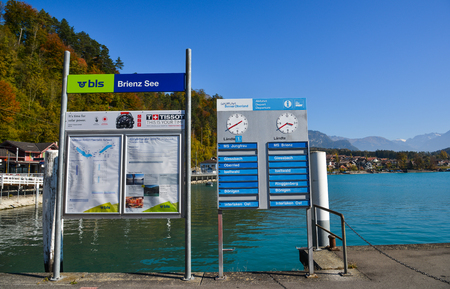 Brienz, Switzerland - Oct 21, 2018. Information boards at tourist jetty in Brienz, Switzerland. Brienz is a beautiful town on the lakeside, attracting many tourists. Редакционное