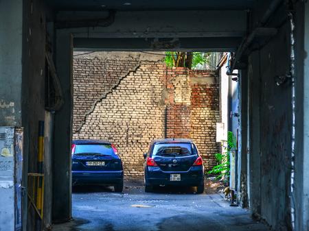 Tbilisi, Georgia - Sep 23, 2018. Cars parking at the old brick house in Tbilisi, Georgia. Editöryel