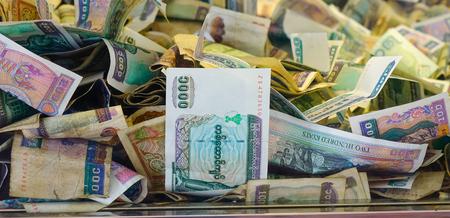 Haufen von burmesischem Geld in Spendenbox an der Kuthodaw-Pagode (Mandalay, Myanmar). Standard-Bild