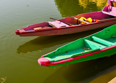Wooden boats waiting for tourists on Gadsisar Lake at sunny day in Jaisalmer, India.