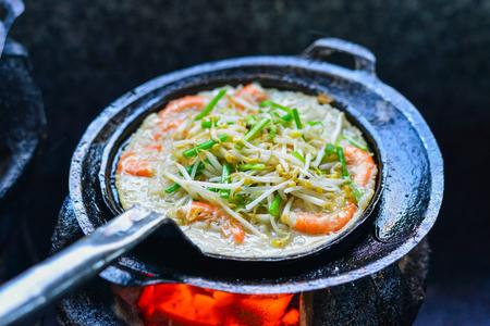 Cooking Vietnamese traditional seafood pancake at old kitchen.