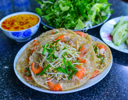 Vietnamese pancake (banh xeo) with fresh vegetable on the table.