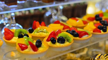 Fresh fruit tarts on sweet table at luxury buffet restaurant. Food concept.