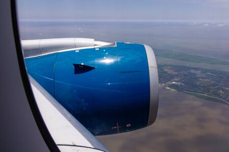 Blue engine of passenger airplane with seascape background in sunny day.