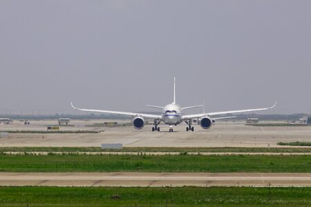 Passenger airplane taxiing on runway of the airport in sunny day.