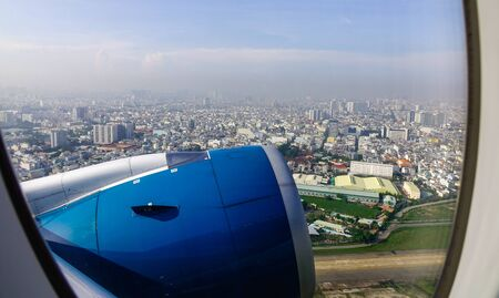 Blue engine of passenger airplane with cityscape background in sunny day.