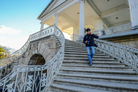 St Petersburg, Russia - Oct 7, 2016. An Asian man walking down the stairs of Catherine Palace in Saint Petersburg, Russia.