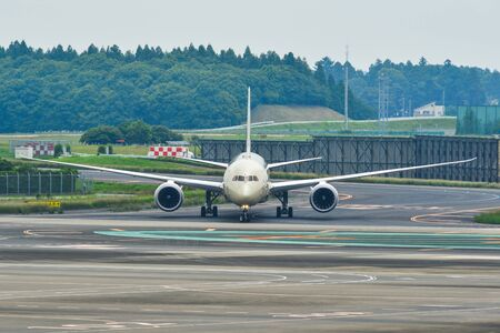 Airplane taxiing on runway of Tokyo Narita Airport (NRT). Narita is one of the busiest airports in Asia.