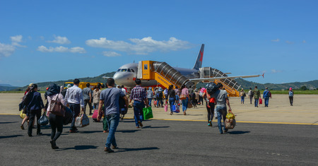 Dalat, Vietnam - Oct 30, 2015. Travelers with luggage at apron area of Dalat - Lien Khuong Airport (DLI), ready to board a Jetstar A320 aircraft.