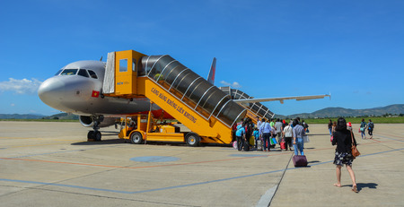 Dalat, Vietnam - Oct 30, 2015. Travelers with luggage at apron area of Dalat - Lien Khuong Airport (DLI), ready to board a Jetstar A320 aircraft. Editorial