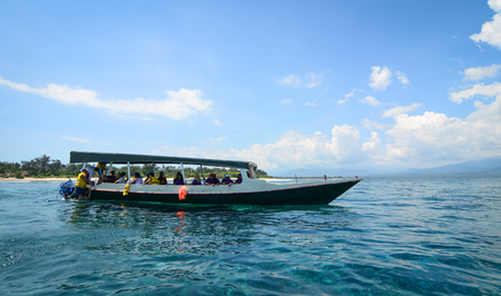 Lombok, Indonesia - Apr 18, 2016. Wooden boat carrying tourists on the sea in Lombok, Indonesia. Lombok, an island next to Bali where the tourism is still in its infancy.