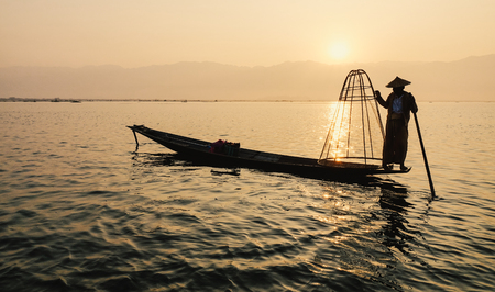 Inle Lake, Myanmar - Feb 16, 2016. Intha man using the unique methods of rowing and catching fish on Inle Lake (Shan State). Editoriali