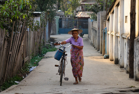 Hsipaw, Myanmar - Feb 23, 2016. A woman with bicycle on street in Hsipaw, Shan State, Myanmar. Shan is Burma largest ethnic nationality group.