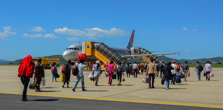 Dalat, Vietnam - Oct 30, 2015. Travelers with luggage at apron area of Dalat - Lien Khuong Airport (DLI), ready to board a Jetstar Airbus A320 aircraft.
