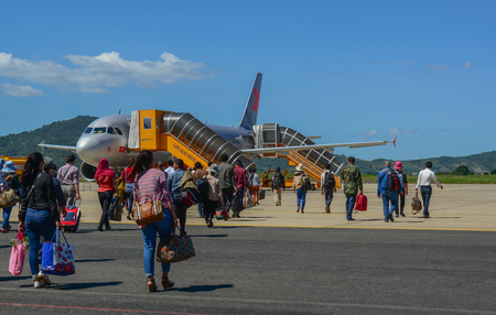 Dalat, Vietnam - Oct 30, 2015. Travelers with luggage at apron area of Dalat - Lien Khuong Airport (DLI), ready to board a Jetstar Airbus aircraft.