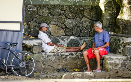 Grand Baie, Mauritius - Jan 11, 2017. Old men sitting and chatting in Grand Baie, Mauritius. Mauritius is known for its beaches, lagoons and reefs. Editorial