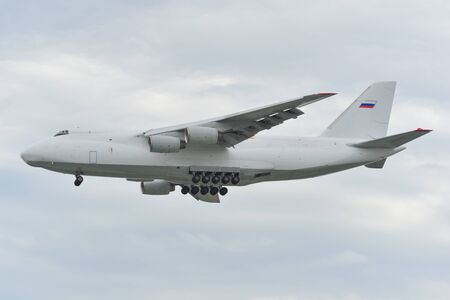 Heavy cargo aircraft landing at the airport in sunny day.