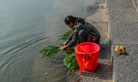 Hunan, China - Nov 6, 2015. A local woman washing vegetable on the river at Fenghuang Old Town in Hunan, China. Editorial