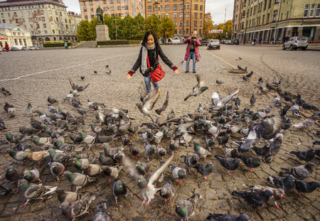 Vyborg, Russia - Oct 6, 2016. People playing with flock of pigeons in a square of Vyborg, Russia. Editorial