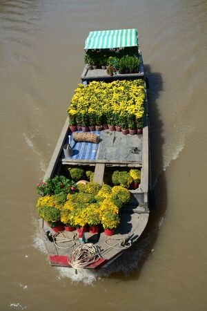 Wooden boats carrying flowers on Mekong River at spring time in Can Tho, Vietnam.