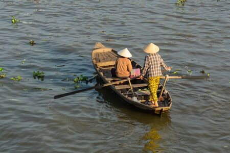 Woman rowing boat on Mekong River in Nga Nam District, Soc Trang, Vietnam. 写真素材