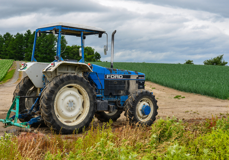 Furano, Japan - Jul 1, 2019. A tractor standing on the field in Furano, Japan. Furano located in the geographical center of Hokkaido Island.