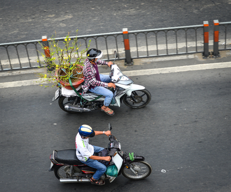 Saigon, Vietnam - Feb 1, 2019. People riding scooters on street in Saigon (Ho Chi Minh). Vietnam has one of the highest motorbike ownership rates worldwide.