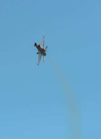 Military aircraft (fighter jet) flying for display in sunny day.