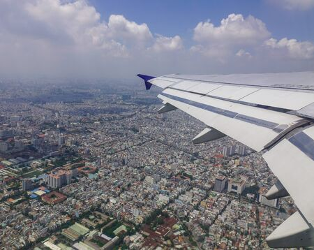 Wing of plane over the city. Scenic view from airplane window.