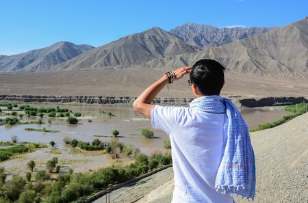 Asian traveler standing on mountain and seeing Indus River in Ladakh, State of Jammu & Kashmir, northern India.