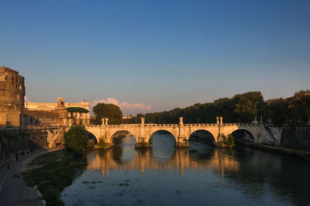 Ancient Sant Angelo Bridge with Tiber River at sunset in Rome, Italy.
