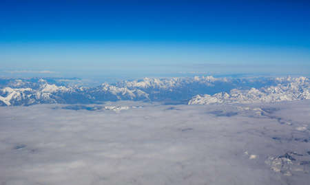 Aerial view above the clouds at mountain peaks covered with snow, lighting by the sun.