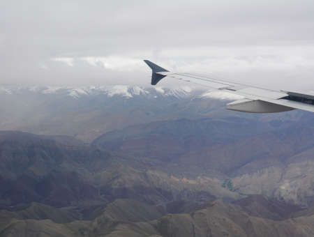 View from airplane window to Hymalaya Mountains and clouds. Travel to Ladakh, North India by airplane.