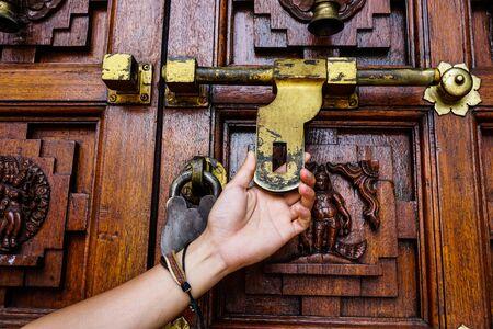 Man holds hand door handle or knocker of ancient wooden door.