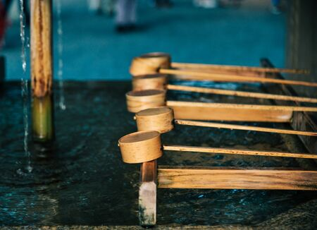 Japanese ladles at Shinto temple in Kyoto, Japan. In Japan, a tsukubai is a washbasin provided at the entrance to holy places for visitors to purify themselves. Imagens