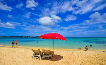 Le Morne, Mauritius - Jan 4, 2017. Red umbrella with relaxing chairs on Mauritius Island. Mauritius is one of the best destinations,  known for its beaches, lagoons and reefs. Archivio Fotografico - 137900887