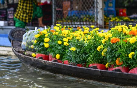 Wooden boat carrying flowers at the floating market in Mekong Delta, Vietnam. Stock Photo