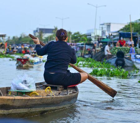 Soc Trang, Vietnam - 19 de enero de 2020. Gente remando en bote de madera en el río Mekong. Los barcos de madera son el principal medio de transporte en el delta del Mekong, Vietnam. Editorial